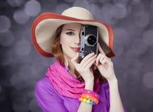 Ragazza divertente della testarossa in cappello con la macchina fotografica e bokeh a fondo immagini stock
