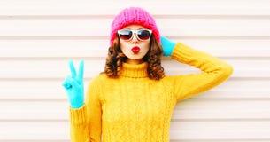 Ragazza divertente di Cooll che soffia le labbra rosse che portano il cappello giallo tricottato variopinto di rosa del maglione fotografie stock libere da diritti