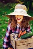 Ragazza divertente felice del bambino in cappello e camicia dell'agricoltore che giocano e che selezionano il raccolto della verd Immagini Stock