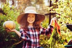 Ragazza divertente felice del bambino in cappello e camicia dell'agricoltore che giocano e che selezionano il raccolto della verd Fotografia Stock