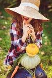 Ragazza divertente felice del bambino in cappello e camicia dell'agricoltore che giocano e che selezionano il raccolto di verdure Fotografie Stock Libere da Diritti