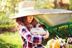 Ragazza divertente felice del bambino in cappello e camicia dell'agricoltore che giocano e che selezionano il raccolto di verdure Immagine Stock