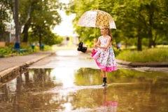 Ragazza divertente felice del bambino con l'ombrello che salta sulle pozze in stivali di gomma ed in vestito dal pois fotografia stock