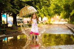 Ragazza divertente felice del bambino con l'ombrello che salta sulle pozze in stivali di gomma ed in vestito dal pois fotografia stock libera da diritti