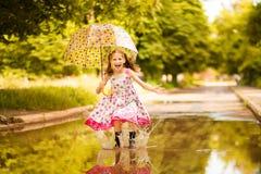 Ragazza divertente felice del bambino con l'ombrello che salta sulle pozze in stivali di gomma ed in vestito dal pois immagine stock