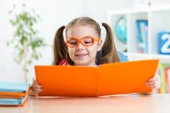 Ragazza divertente felice del bambino in vetri che legge un libro Immagini Stock Libere da Diritti