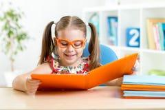 Ragazza divertente felice del bambino in vetri che legge un libro Fotografia Stock