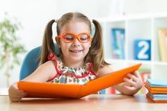 Ragazza divertente felice del bambino in vetri che legge un libro Fotografie Stock Libere da Diritti