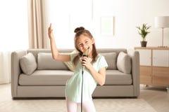 Ragazza divertente sveglia con il microfono immagini stock