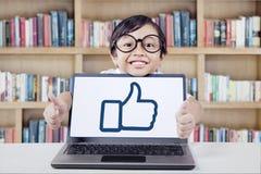 Ragazza dolce che mostra simbolo GIUSTO con il computer portatile Fotografie Stock Libere da Diritti