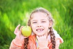 Ragazza dolce con un toth caduto che tiene una mela in sua mano Fotografie Stock