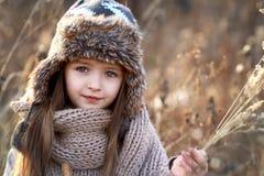 Ragazza dolce in un cappuccio con i cervi in autunno in un campo di erba asciutta Fotografia Stock Libera da Diritti