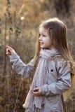 Ragazza dolce in un cappuccio con i cervi in autunno in un campo di erba asciutta Immagini Stock