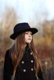 Ragazza dolce in un cappuccio con i cervi in autunno in un campo di erba asciutta Fotografie Stock