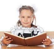 Ragazza dolce in un uniforme scolastico che tiene un libro aperto Immagine Stock