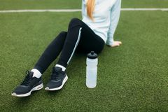 Ragazza dopo l'esercizio, acqua potabile sul campo di football americano Ritratto di bella ragazza in abiti sportivi fotografia stock