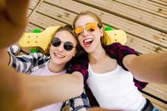 Ragazza due in attrezzatura dei pantaloni a vita bassa che fa selfie mentre trovandosi con sul pilastro di legno fotografie stock