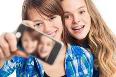 Ragazza due che si fotografa su un telefono cellulare Fotografia Stock