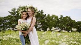 Ragazza due in corona con il mazzo dei fiori che abbraccia mentre posando sul campo verde Giovane modello di moda che posa con archivi video