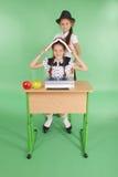 Ragazza due in un uniforme scolastico che si siede ad uno scrittorio e che legge un libro Immagine Stock