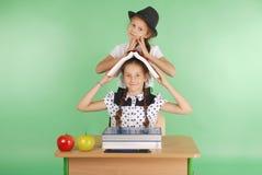Ragazza due in un uniforme scolastico che si siede ad uno scrittorio e che legge un libro Fotografie Stock Libere da Diritti