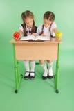 Ragazza due in un uniforme scolastico che si siede ad uno scrittorio e che legge un libro Fotografia Stock Libera da Diritti