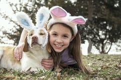 Ragazza e cane con le orecchie del coniglietto sopra Immagine Stock