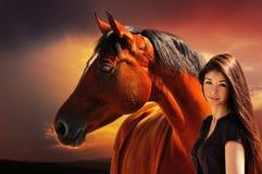 Ragazza e cavallo sui precedenti del cielo drammatico Fotografia Stock