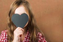 Ragazza e cuore nero dell'ardesia La ragazza sviluppa una fisiognomica, gli smorfie e un cuore per un'iscrizione Concetto di San  immagini stock libere da diritti