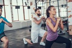 Ragazza e due tipi che fanno gli esercizi di affondo in palestra immagine stock
