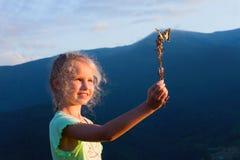 Ragazza e farfalla in montagna di tramonto fotografia stock libera da diritti