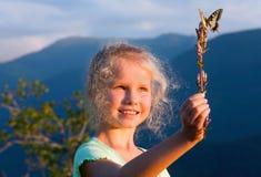 Ragazza e farfalla in montagna di tramonto immagine stock