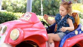 Ragazza e giri del bambino un'automobile elettrica nel parco per spettacolo archivi video