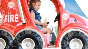 Ragazza e giri del bambino un'automobile del fuoco nel parco per spettacolo Attrazioni per i bambini archivi video