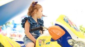 Ragazza e giri del bambino un motociclo elettrico nel parco per spettacolo archivi video