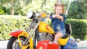 Ragazza e giri del bambino un motociclo elettrico nel parco per spettacolo stock footage