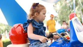 Ragazza e giri del bambino un motociclo elettrico nel parco per spettacolo video d archivio
