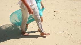 Ragazza e Guy Walk Barefoot biondi lungo la spiaggia stock footage