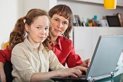 Ragazza e la sua madre con il computer portatile nel paese Fotografia Stock Libera da Diritti