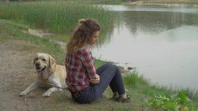 Ragazza e labrador della testarossa sul lago stock footage