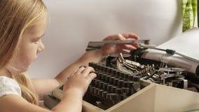 ragazza e macchina da scrivere tipi del bambino immagini stock libere da diritti
