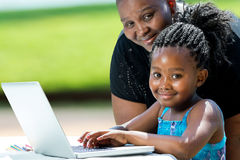 Ragazza e madre africane dolci con il computer portatile Fotografia Stock Libera da Diritti
