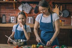 Ragazza e madre che cucinano insieme insalata fotografia stock