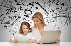 Ragazza e madre con la compressa ed il computer portatile Immagini Stock