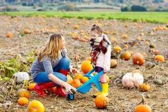 Ragazza e madre del bambino divertendosi sulla zucca Immagini Stock