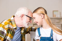 Ragazza e nonno felici in occhiali che toccano le fronti e che si sorridono Immagine Stock Libera da Diritti