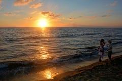 Ragazza e ragazzo al tramonto sulla spiaggia Fotografia Stock Libera da Diritti
