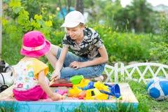Ragazza e ragazzo che giocano nella sabbiera Fotografie Stock Libere da Diritti