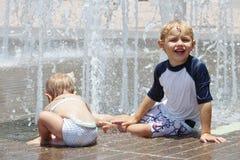 Ragazza e ragazzo che giocano in un cuscinetto della spruzzata Fotografia Stock