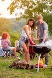 Ragazza e ragazzo che preparano barbecue immagini stock